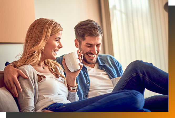 Man and woman sitting on couch and drinking coffee